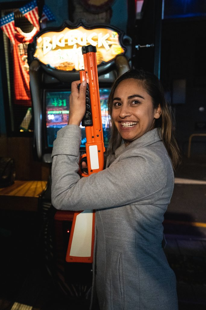 woman playing shooting arcade game
